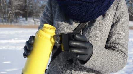 couro : hands with leather gloves pour hot tea coffee from yellow thermos and drink it in winter. Vídeos
