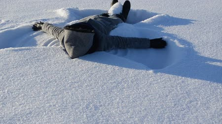 snow angel : woman make angel silhouette move hands and legs lie on winter snow. Stock Footage