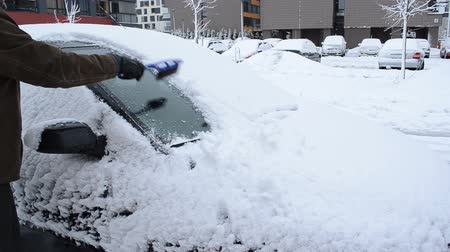 clothing : man hand removing snow from car front window with a brush in winter. Stock Footage