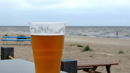 cervejaria : plastic tumbler of beer stand on beach pub table on background of sea. Stock Footage
