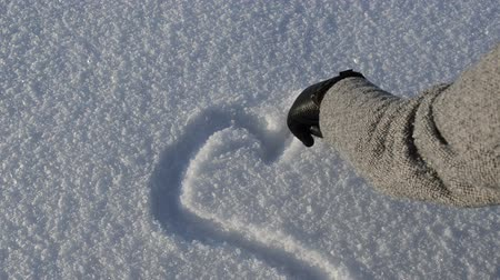 kreslit : woman hand with leather gloves draw romantic heart shape on light snow in cold beautiful winter day.