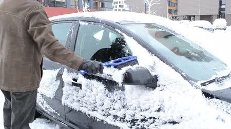 don : man remove clean snow from car window with a brush in flat house parking lot yard in winter. Stok Video