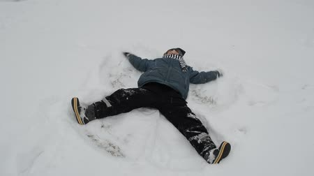 sporty zimowe : little boy rejoiced winter day and make an angel snow bank