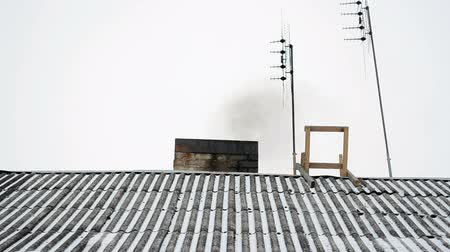 átfedés : old house slate roof covered with snow and smoke rise from chimney near antenna in winter.
