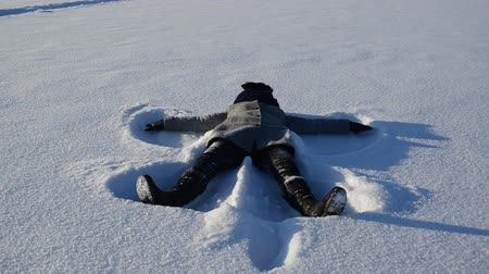 snow angel : woman make angel silhouette moving hands and legs lie on winter snow in cold sunny day. Stock Footage