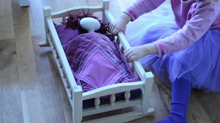 boneca : a little girl cradled by her doll lying on a wooden bed with a soft featherbed Vídeos