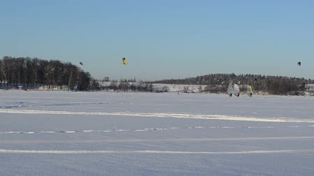 três pessoas : three people ice surfing sailing on boats winter frozen lake and kiteboarding kiting with snowboards in winter.  modern recreation hobby. Vídeos
