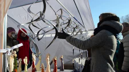 cortes : VILNIUS, LITHUANIA - MARCH 02: Young woman spin silver wind whirligig toys and angel silhouette outdoor spring fair market event on March 02, 2012 in Vilnius. Merchants polite smile talk with clients. Vídeos