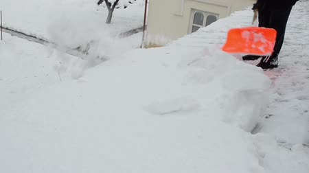 Łopata : risky winter work. worker man in black with orange shovel clean dig snow from house roof. Wideo