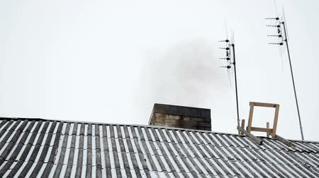 átfedés : old house slate roof covered with snow and dark smoke rise from chimney near antenna in winter.