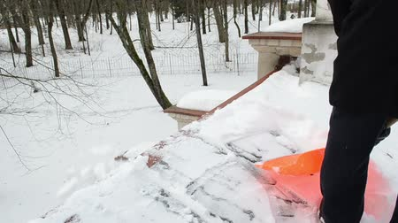 deep snow : closeup of man with plastic orange shovel tool push clean snow from roof. winter works. Stock Footage