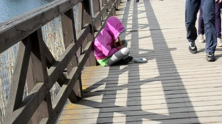 fife : Young girl with fife pipe play melody begging for money on wooden bridge and people tourist passing. Poverty.