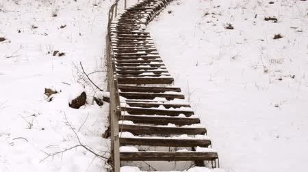 yolları : Panorama of wooden stairs with railings on huge steep hill covered with snow in winter park.
