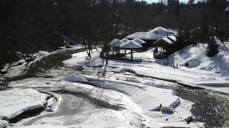 ártico : frozen river bay water and small wooden houses on bank with straw roof covered with snow.