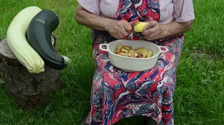 peeler : senior woman with apron hands peel shave fresh potato with knife. healthy natural food zucchini on tree stump.