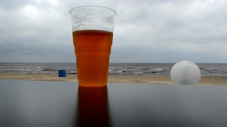 içme : plastic mug of beer stand on beach pub table on background of sea. Stok Video