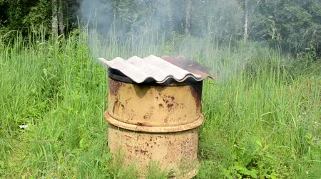 strawberry oil : smoke rises from old rural handmade barrel smokehouse asbestine slate roof. Stock Footage
