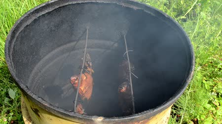 dorsal : ecologic fish hang smoke in smokehouse made of old rusty barrel. Stock Footage