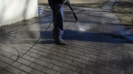 temizleme maddesi : gardener with jet of water wash away trash from the tile. Stok Video