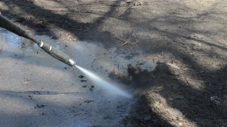 arruela : housewife with a strong jet of water washes the dirt from the asphalt Stock Footage