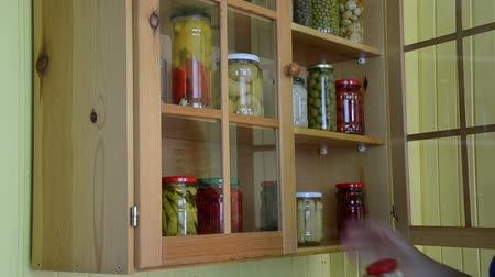 conservado : hand opens a wooden cupboards door pushes jars of canned vegetables puts jar canned garlic