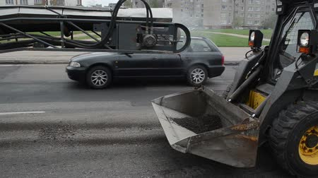 оставаться : Asphalt remains dirt loading to small rv bobcat truck in street and cars passing. Industrial road repair. Стоковые видеозаписи