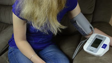 sphygmomanometer : Woman measuring blood pressure on hand with special tool. Health care at home. Stock Footage