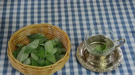 шелуха : Housewife hand preparing healthy natural mint herb tea.