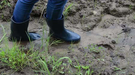 step : Woman legs with gumboots rubber boots walk on wet dirt soil mud and leaves footprints marks.