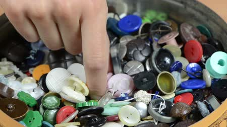 времяпровождение : Woman hand pick collection of buttons used in manufacturing garments clothes for sales.