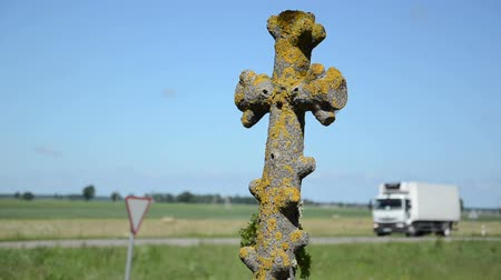 temető : Retro mossy stone cross closeup and car drive risk concept.