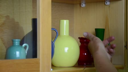 простота : Woman girl hand take small colorful crockery vases decorations from wall cabinet and close door.