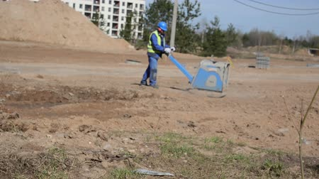 compares : worker in blue workwear with a heavy device compares the rough surface of the earth