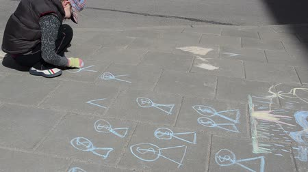 мел : girl with hat drawing with blue piece of chalk of blacktop in the yard