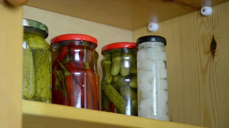 conservado : hand takes three small jars of pickled onions garlic and capers from the shelf