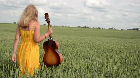 cantora : through the green corn goes a girl with yellow dress guitar in hand sits on a stump hidden in corn Vídeos