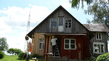 ремонтировать : Painter farmer man with hat on ladder paint old wooden rural homestead house wall with brush paintbrush.