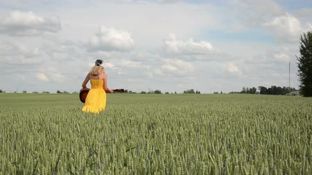 honesto : pretty girl in dress and headscarf play guitar walking in field. Vídeos