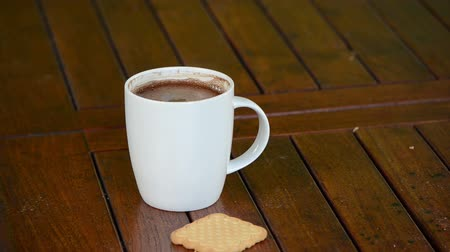 xícara de café : Cup of steaming hot coffee in white cup and cookie biscuit on table in outdoor bower.