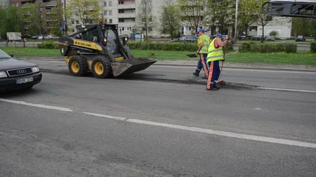 оставаться : VILNIUS, LITHUANIA - CIRCA MAY 2013 - Workers with uniform and shovels load asphalt remain to small rv bobcat on street lane  circa May 2013 in Vilnius, Lithuania.