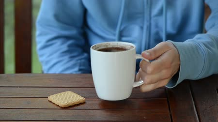 xícara de café : Hand put cup of steaming hot morning coffee near cookie biscuit on table.