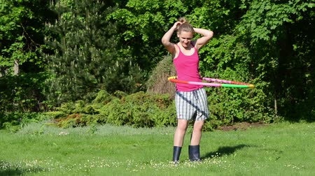 abroncs : cheerful smiling woman turn spin hula hoop ring on waist in beautiful morning garden.
