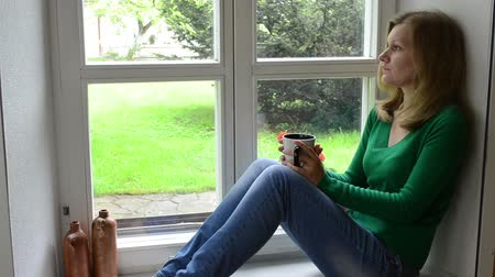 aggódó : Sad worried woman girl sit on wooden window sill and drink coffee tea.