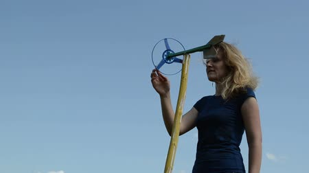 fırıldak : beautiful woman play with spinning windmill pinwheel toy on background of blue sky. Stok Video