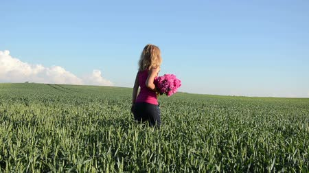 mavi arka : blonde girl with big pink peonies bouquet goes wide field of green rye