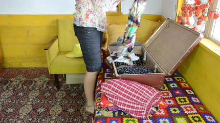 favori : Girl on colorful room sofa unpacking clothes from suitcase. Visiting grandmother in rural village.