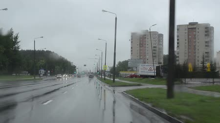 perigoso : cars drive on urban city road and rain fall. Front automobile window windscreen view and wipers work. Bad weather conditions in autumn. Vídeos