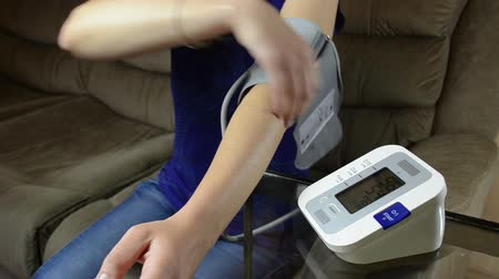 take blood : Woman take off pressure measure tool from hand and turn it off.
