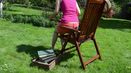 шорты : Woman in shorts sit on wooden chair and read book. Studying in garden.