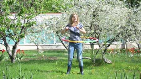 abroncs : woman spin turn colorful hula hoop ring on waist near beautiful blossom fruit tree and tulips.